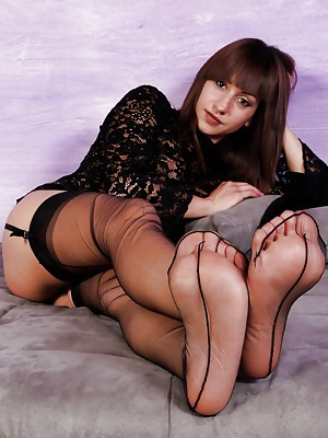Gorgeous brunette in sexy nylons shows her perfect soles