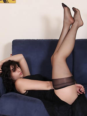 Hot brunette in black pantyhose play with her feet